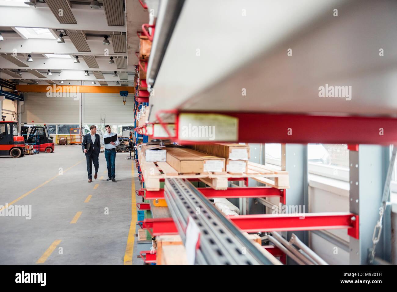 Two men walking and talking in factory shop floor - Stock Image