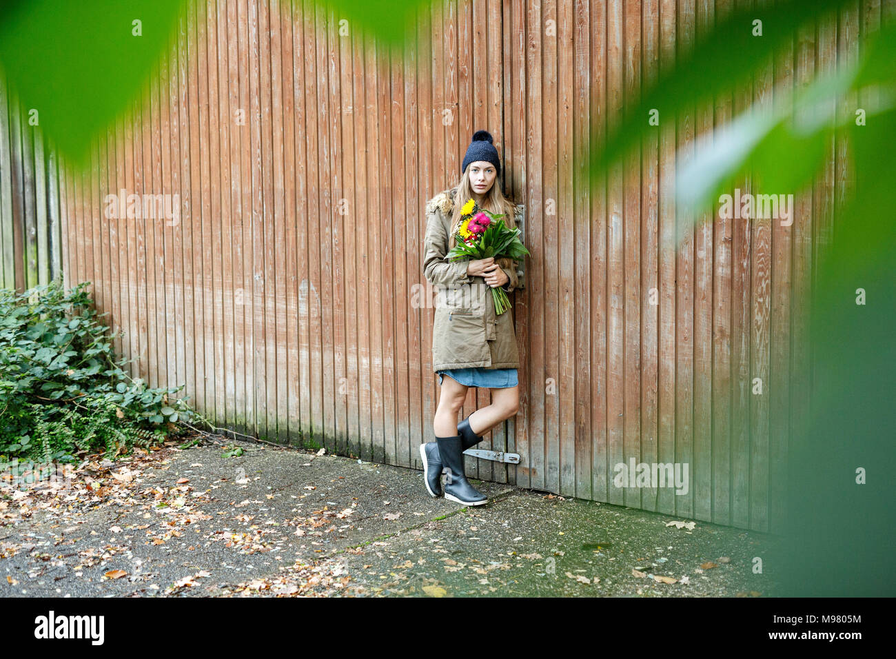Portrait of young woman standing at wooden wall holding bunch of flowers - Stock Image