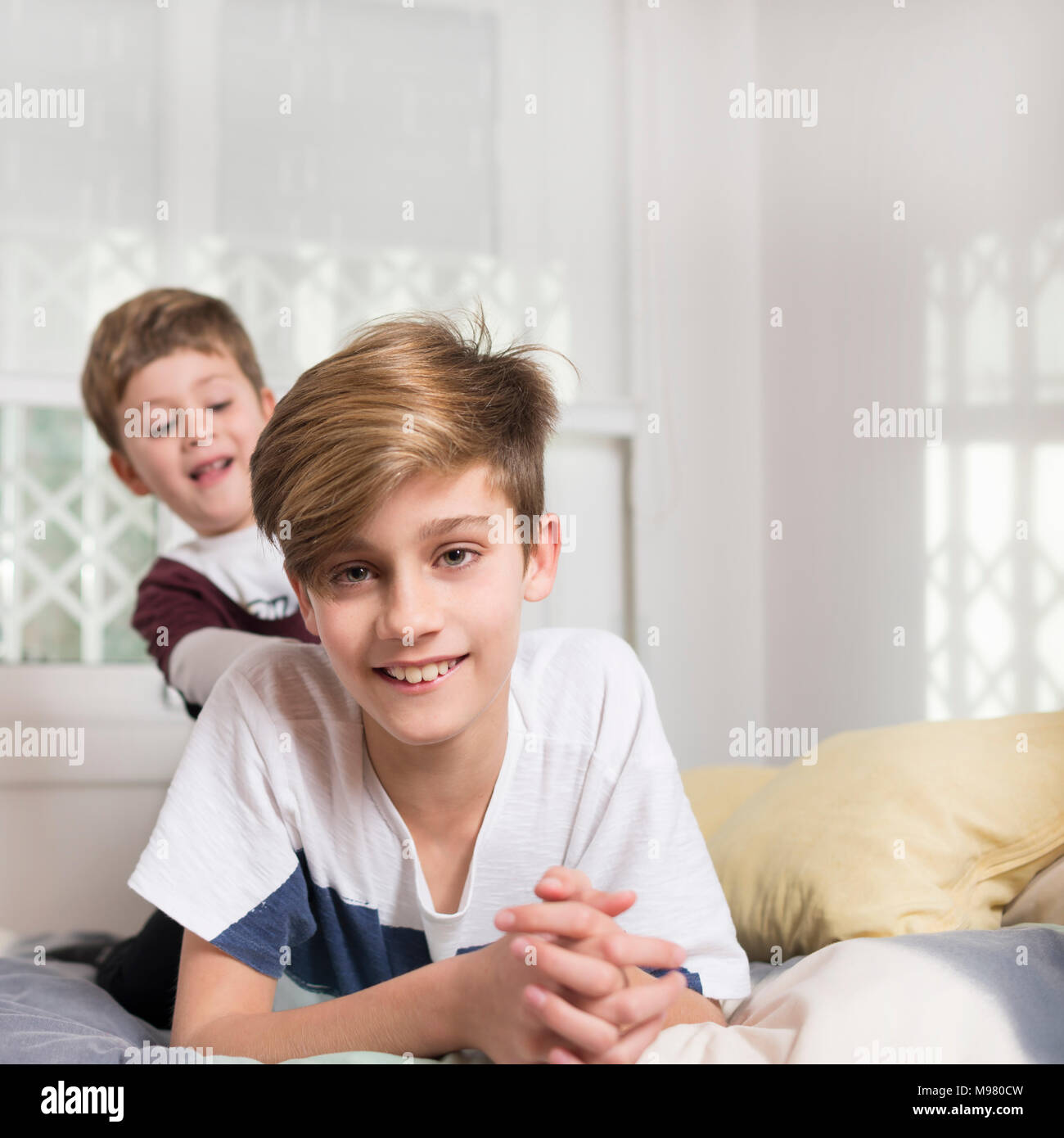 Portrait of smiling boy with younger brother lying on bed at home - Stock Image
