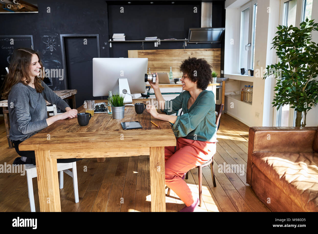 Two happy young women with camera in modern office - Stock Image