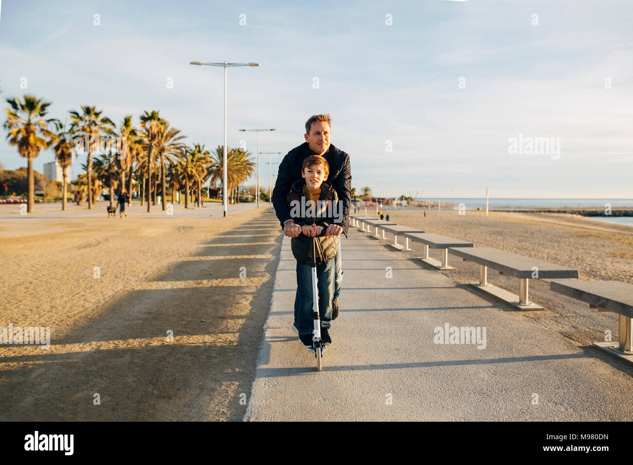 Father and son riding scooter on beach promenade at sunset - Stock Image