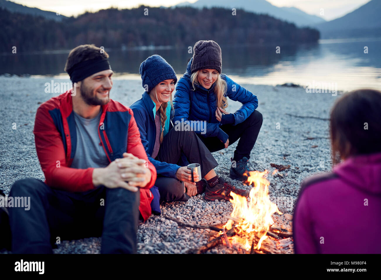 Smiling friends sitting around campfire at lakeshore - Stock Image
