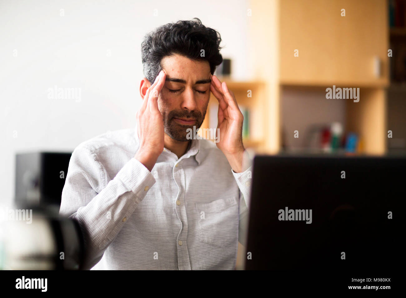 Portrait of businessman with hands on his temples at desk in office - Stock Image