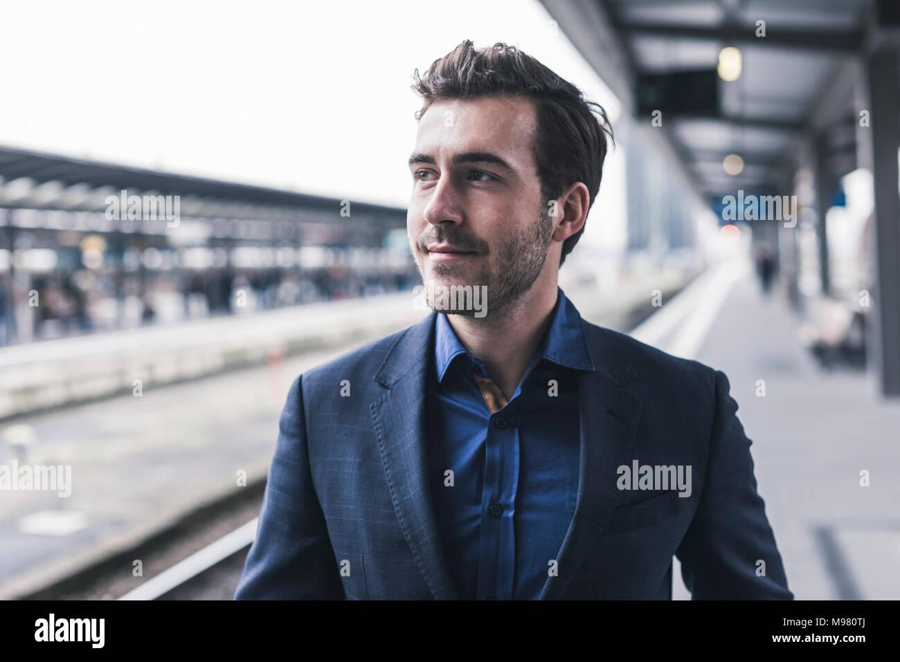 Young businessman waiting at station platform - Stock Image