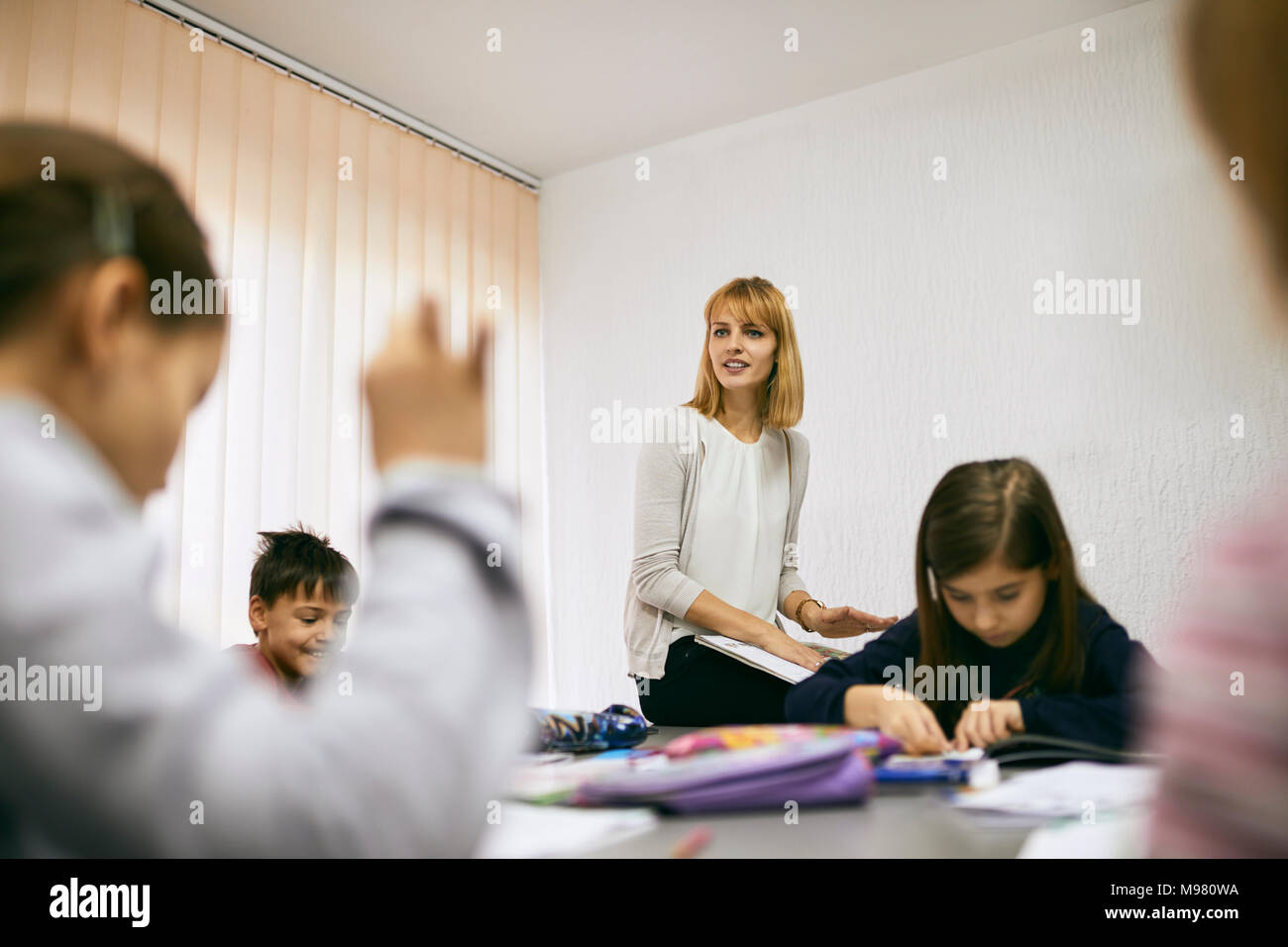 Teacher with students in class - Stock Image