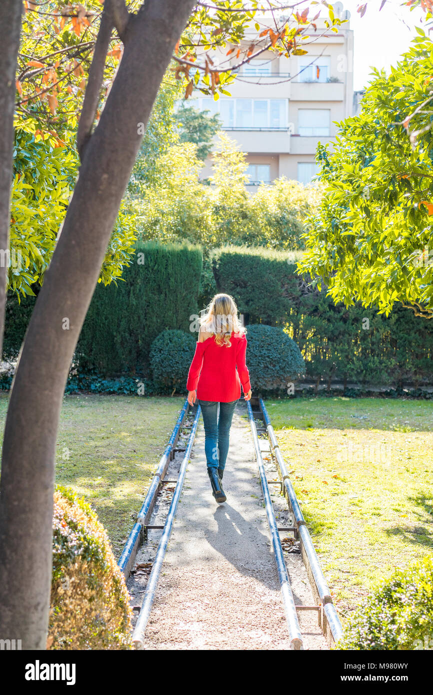 Young woman walking on path in a garden - Stock Image