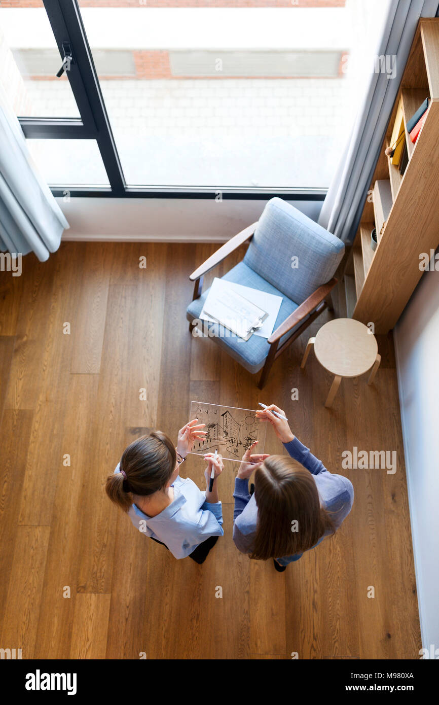Group of female architects having a meeting, seen from directly above - Stock Image
