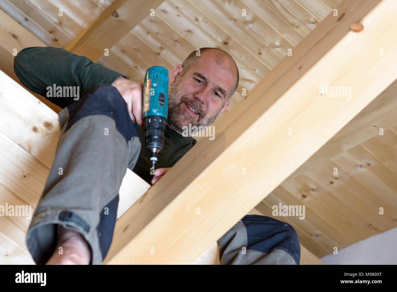 Mann mit Bohrer, Innenausbau Dachgeschoss, Boden legen, Holzhaus, Bayern, Deutschlaned - Stock Image