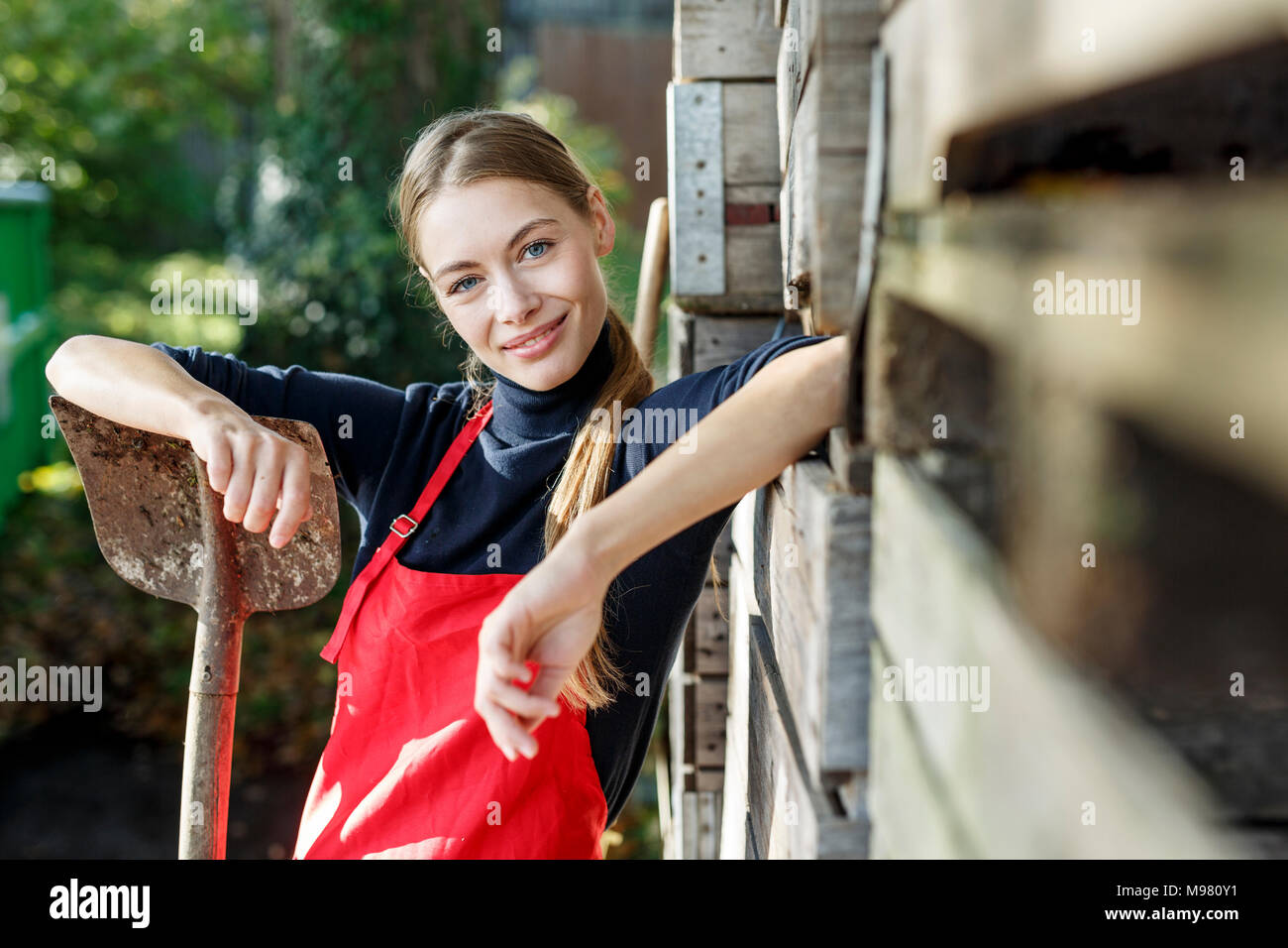 Portrait of smiling young woman with spade - Stock Image