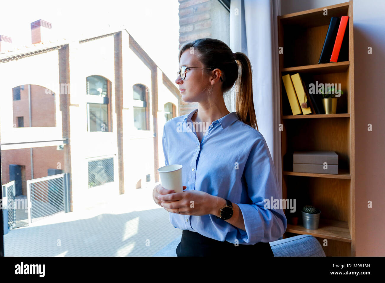 Young woman with coffee cup looking out of office window - Stock Image
