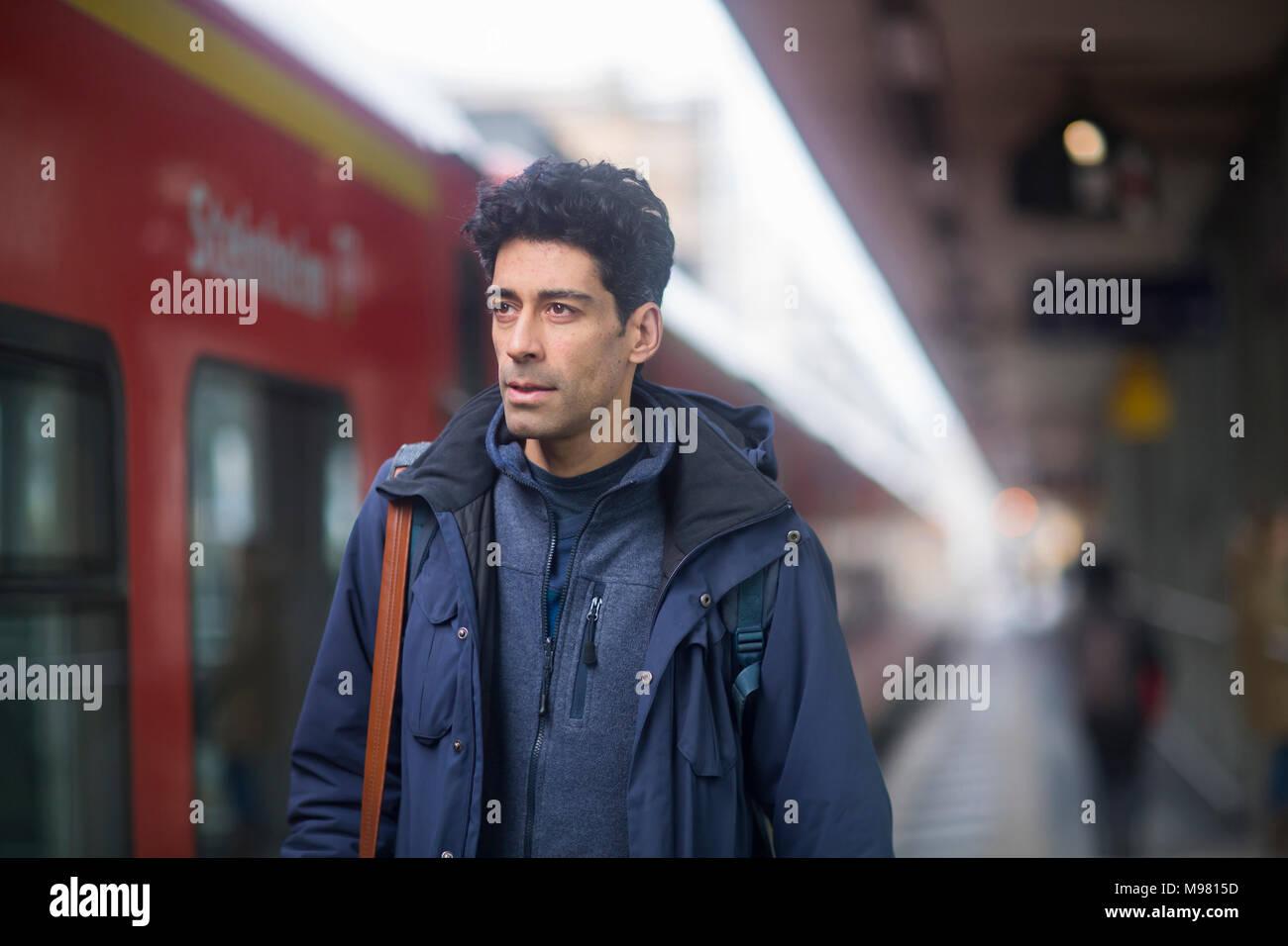 Portrait of man with backpack on platform - Stock Image