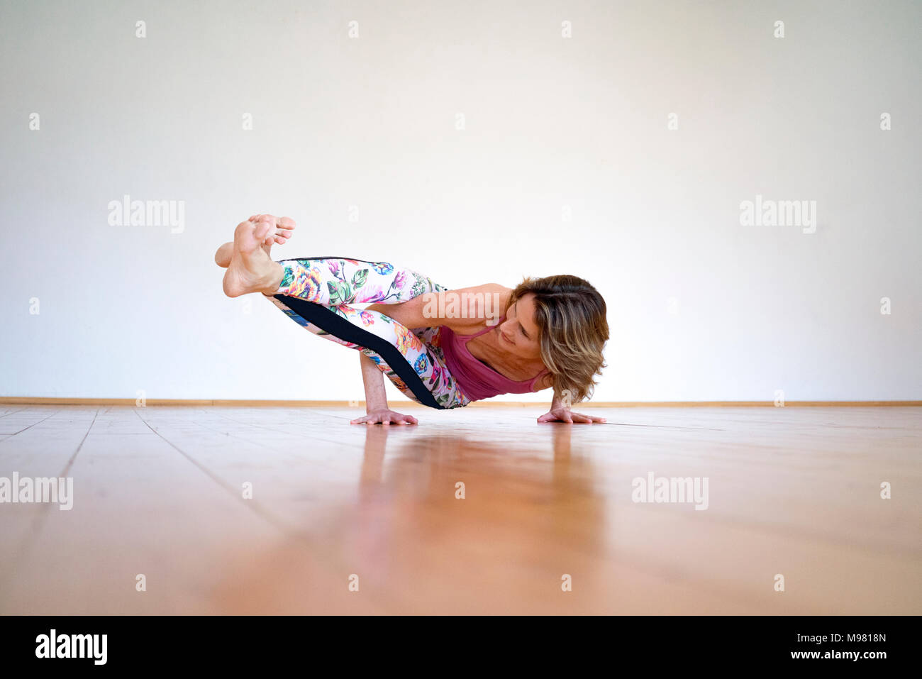Mature woman practicing yoga on floor in empty room Stock Photo