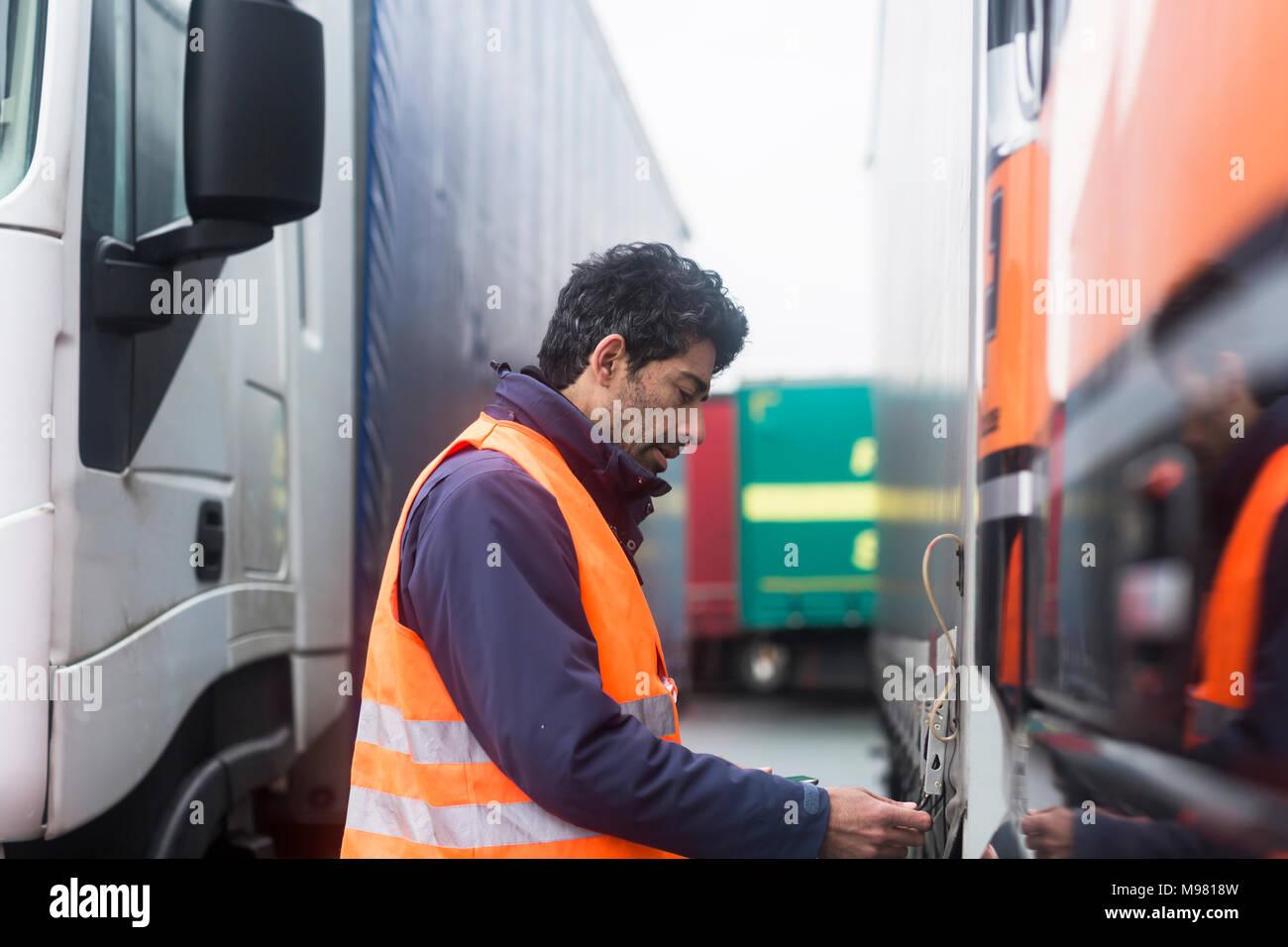 Man wearing reflective vest examining truck - Stock Image