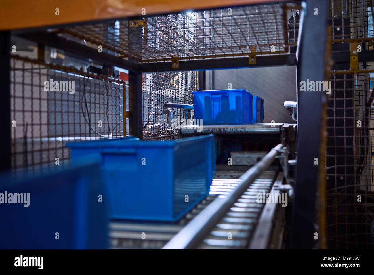 Blue boxes on conveyor belt - Stock Image