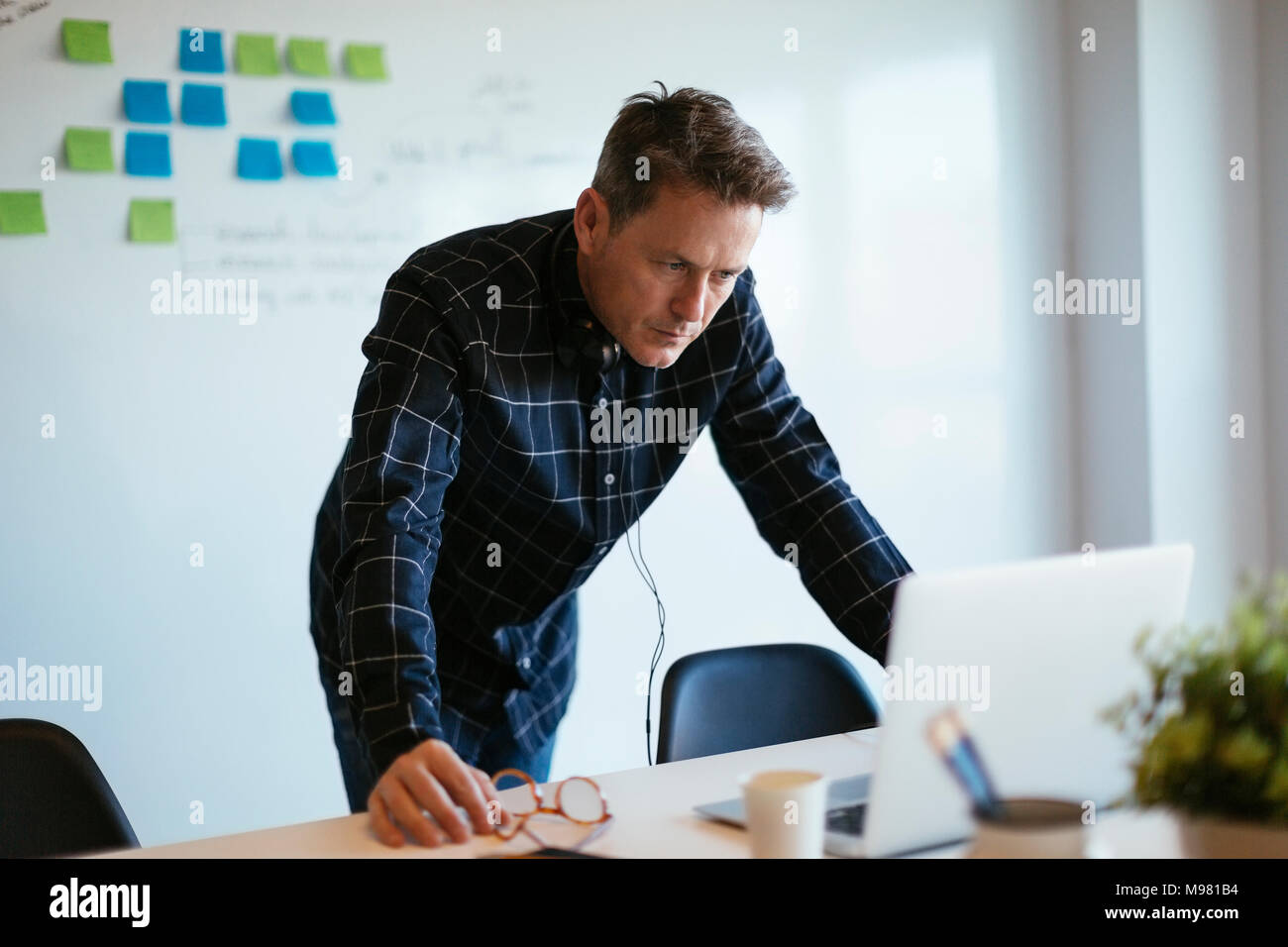 Businessman standing at desk in office looking at laptop - Stock Image