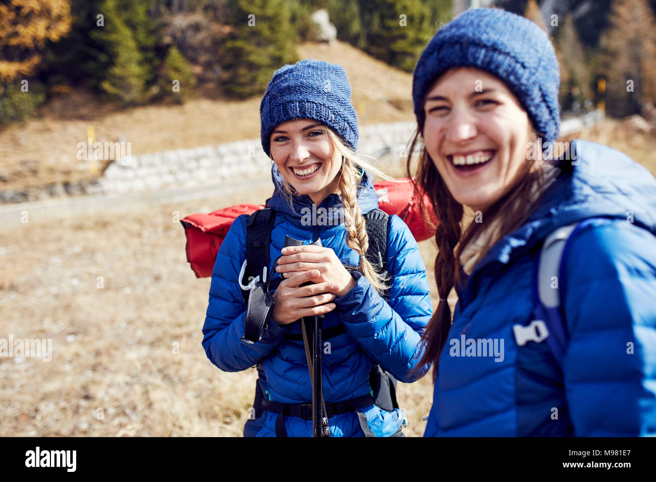 Two laughing young women hiking in the mountains - Stock Image