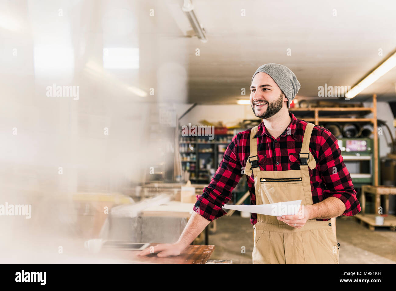 Happy worker holding draft in workshop - Stock Image