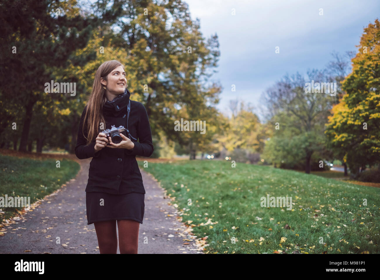 Young woman with camera walking in autumnal park - Stock Image