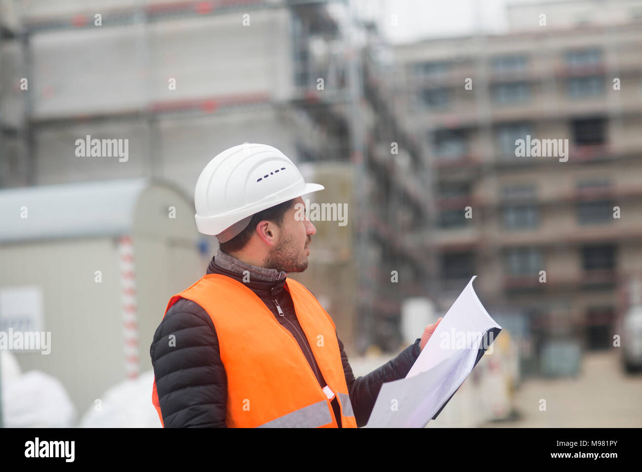 Man with plan wearing safety vest and hard hat at construction site - Stock Image