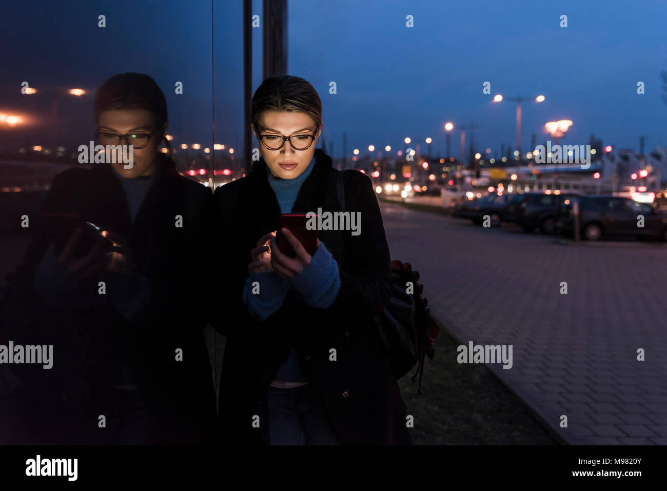 Young woman leaning against glass front at night using cell phone - Stock Image