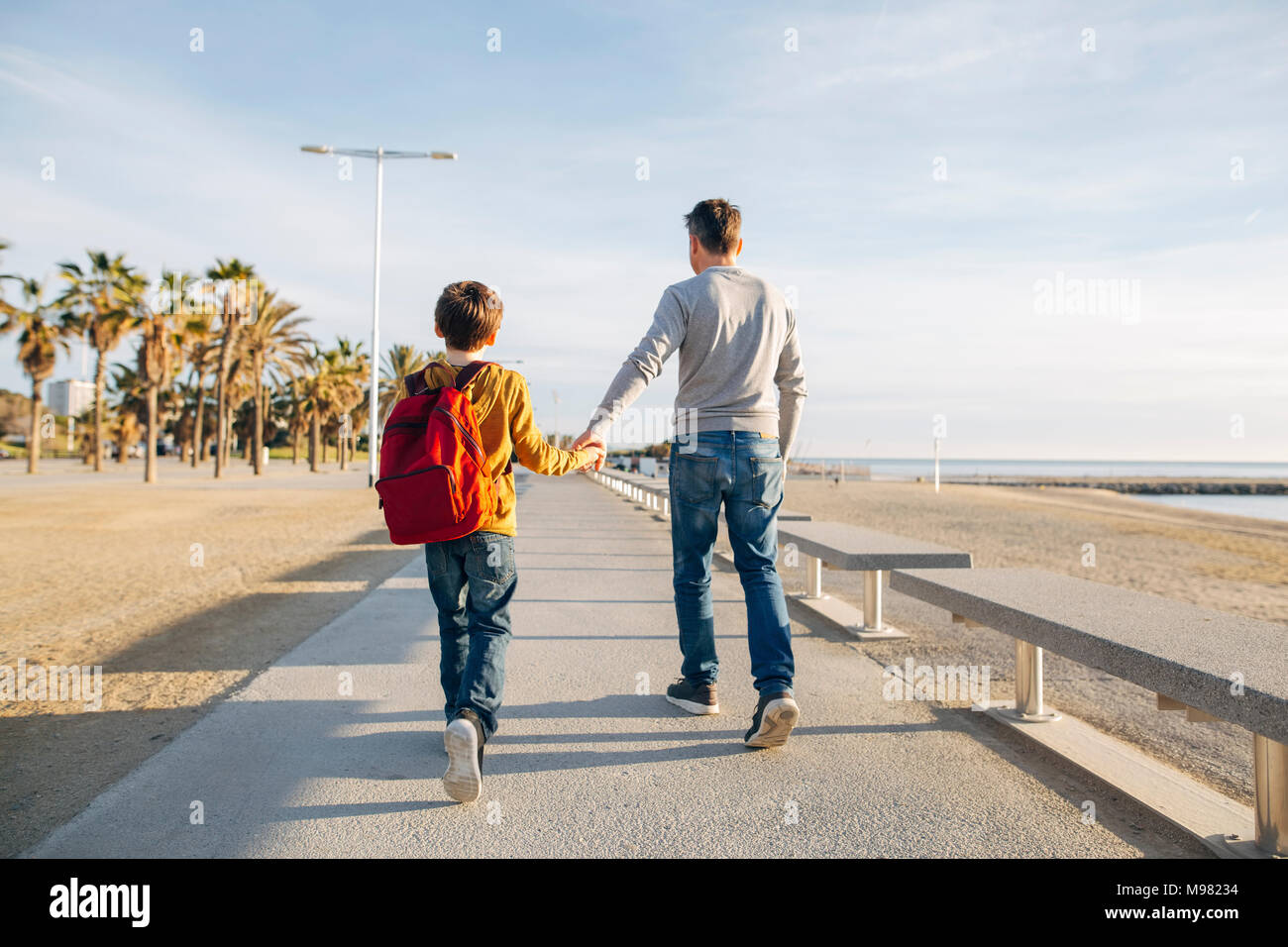 Father and son walking on beach promenade - Stock Image