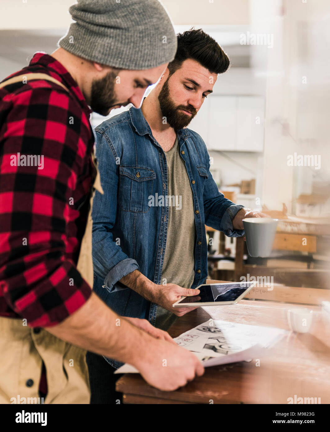 Two men with tablet looking at draft in workshop - Stock Image