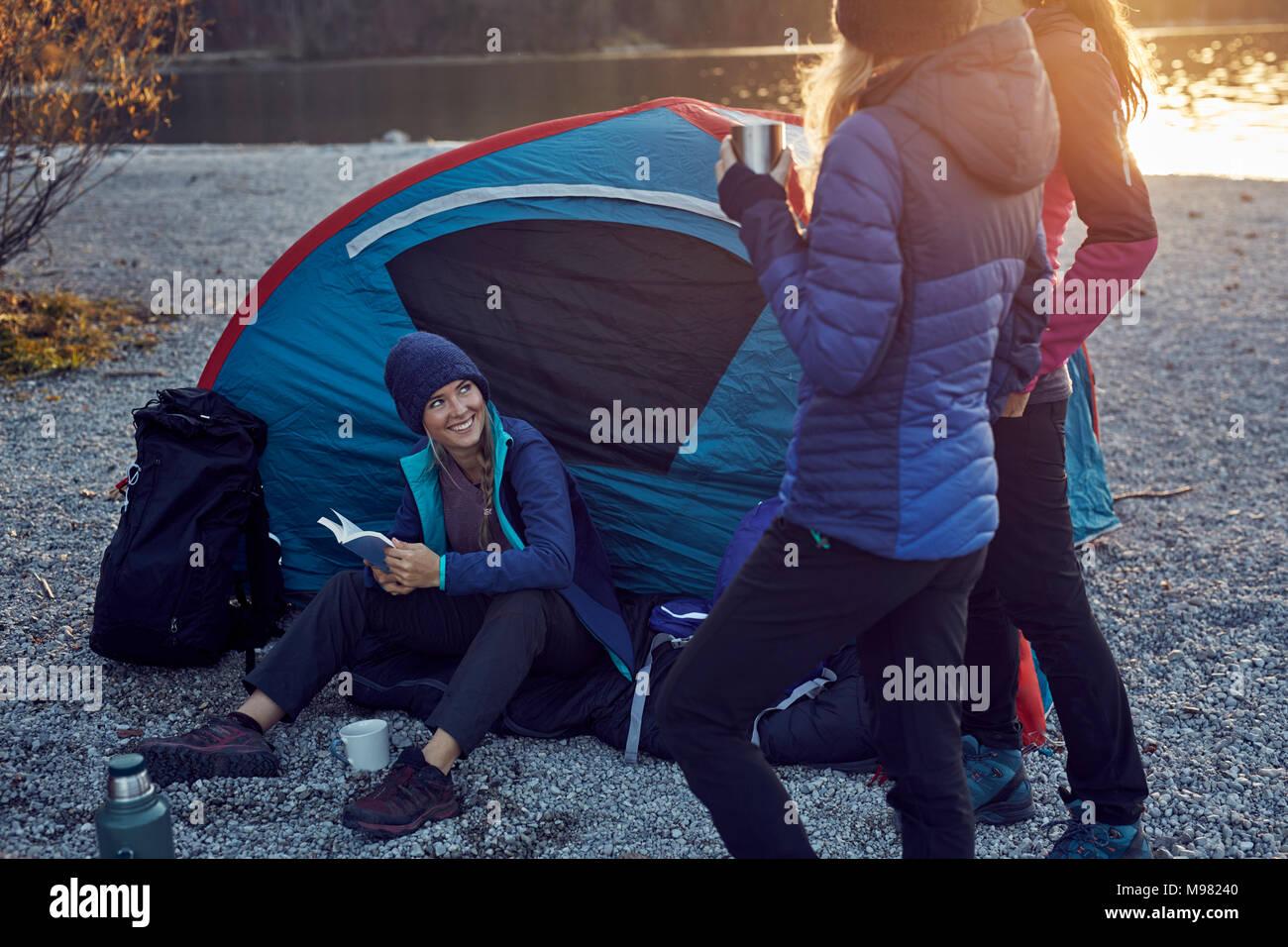 Group of hikers camping at lakeshore at sunset - Stock Image