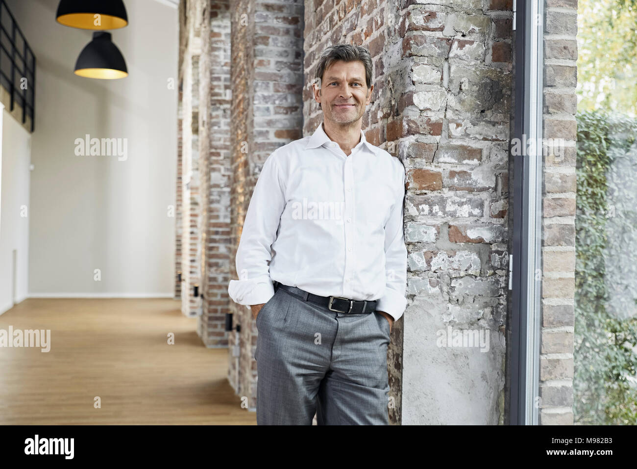 Portrait of smiling businessman leaning against brick wall in modern office - Stock Image