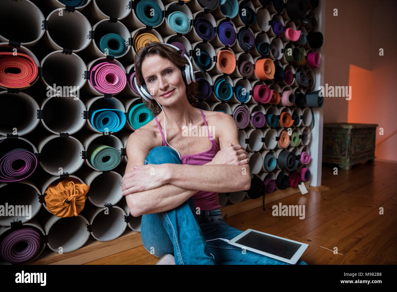 Portrait of smiling mature woman listening to music in front of assortment of yoga mats - Stock Image