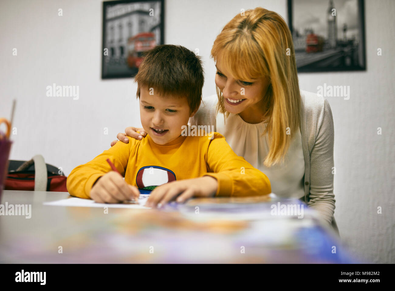 Teacher helping student at desk in class - Stock Image