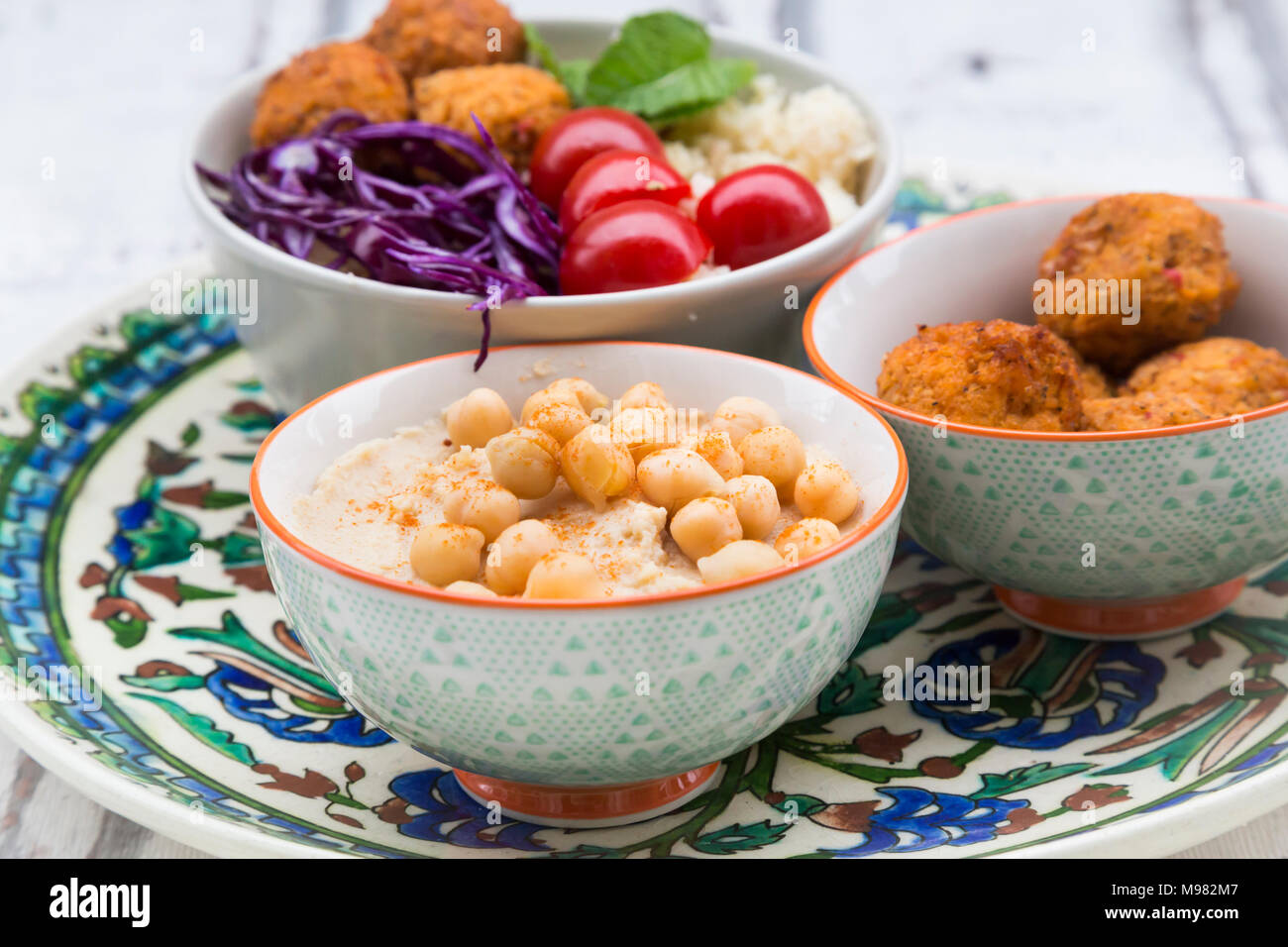 Hummus, sweet potato balls, Couscous and vegetables in bowls - Stock Image