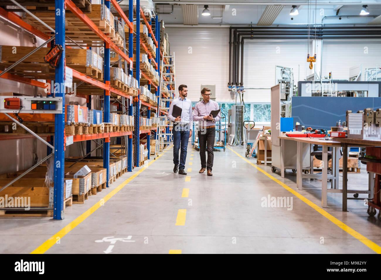 Two men walking in factory - Stock Image