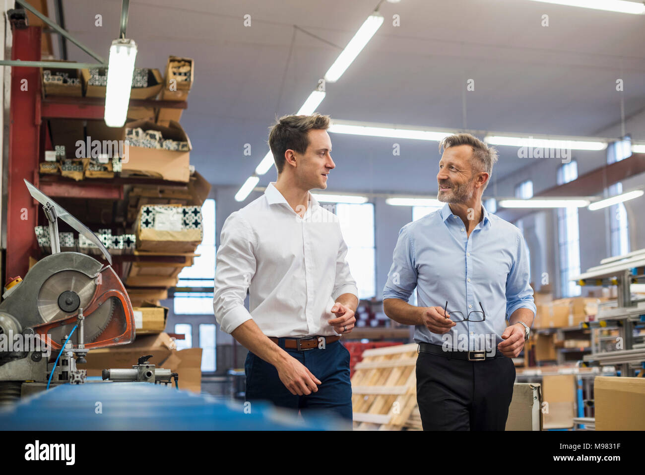 Two businessmen walking and talking in factory storeroom - Stock Image