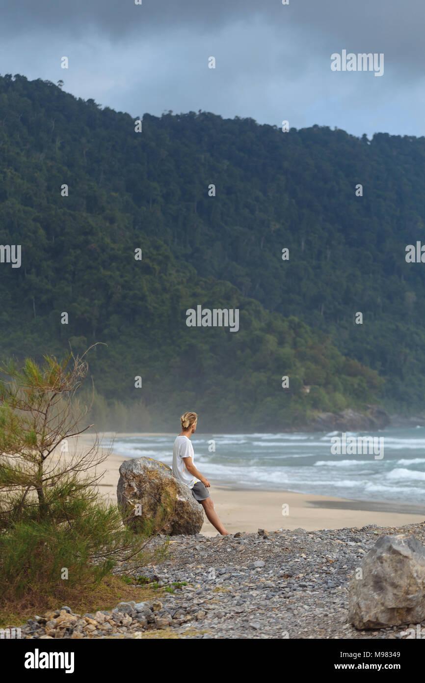 Indonesia, Sumatra, young man at ocean coastline - Stock Image