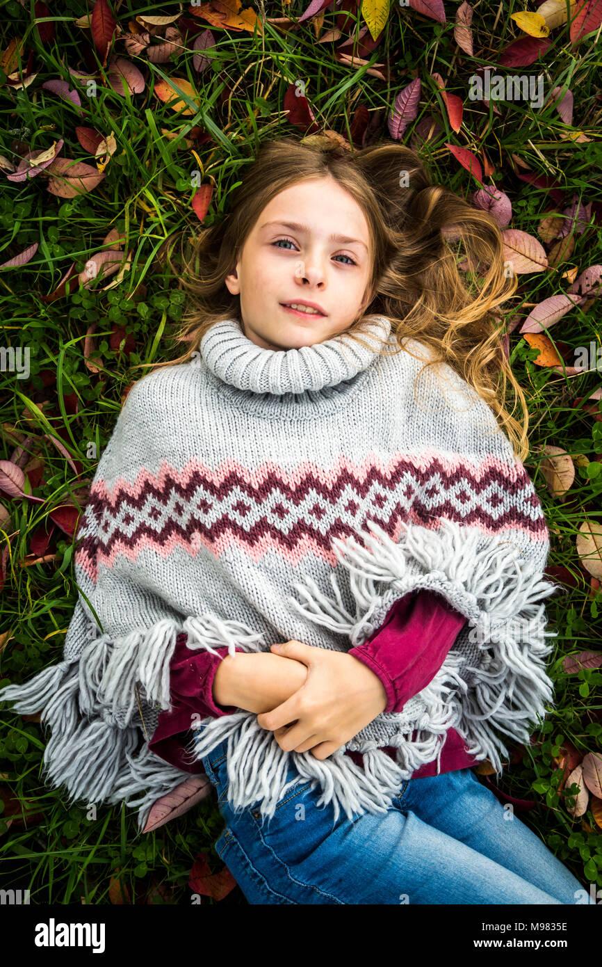 Portrait of girl wearing poncho lying on autumnal meadow - Stock Image