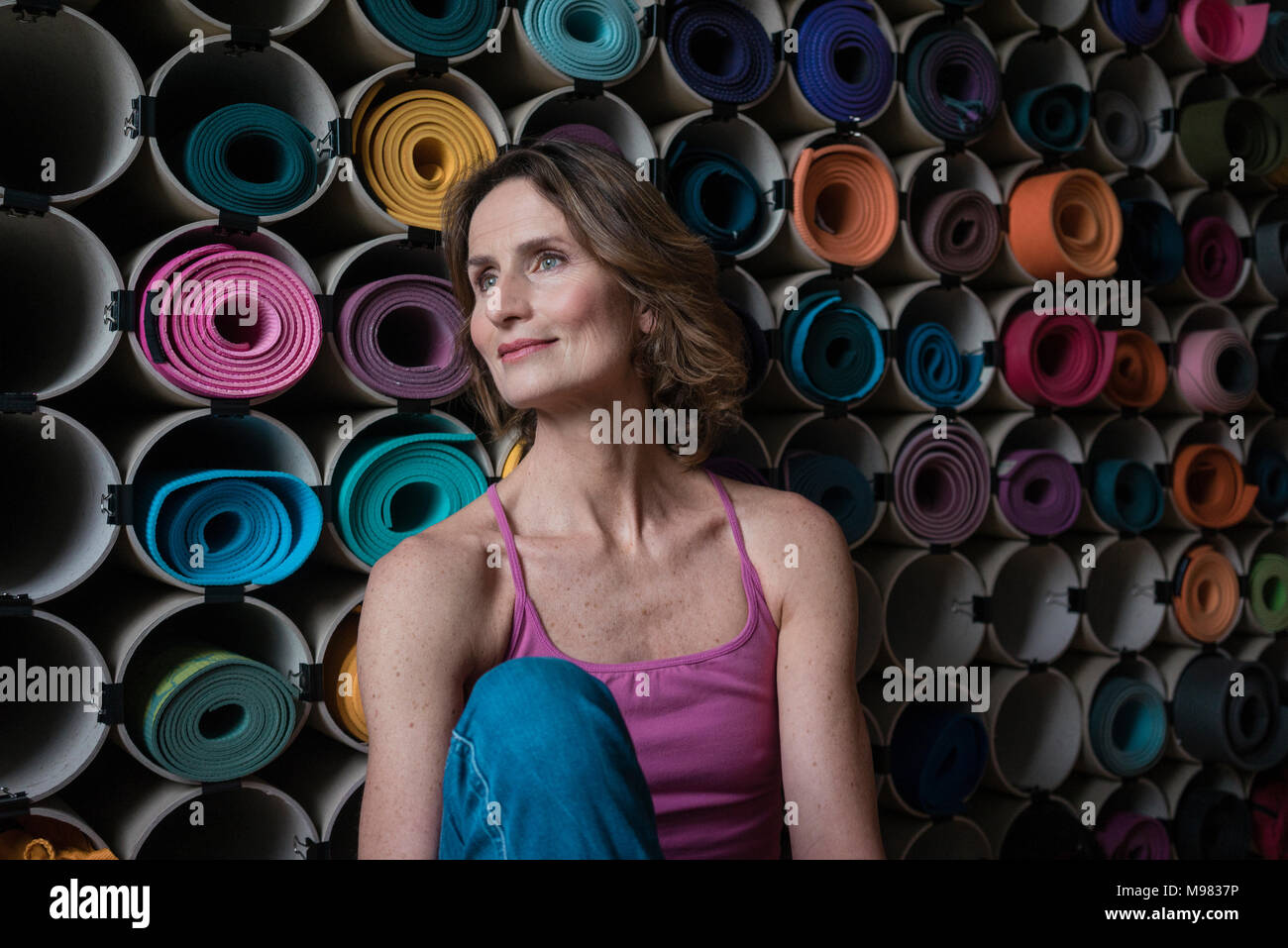 Smiling mature woman in front of assortment of yoga mats - Stock Image