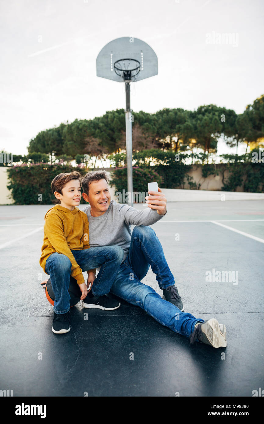 Father and son sitting on basketball outdoor court taking a selfie - Stock Image