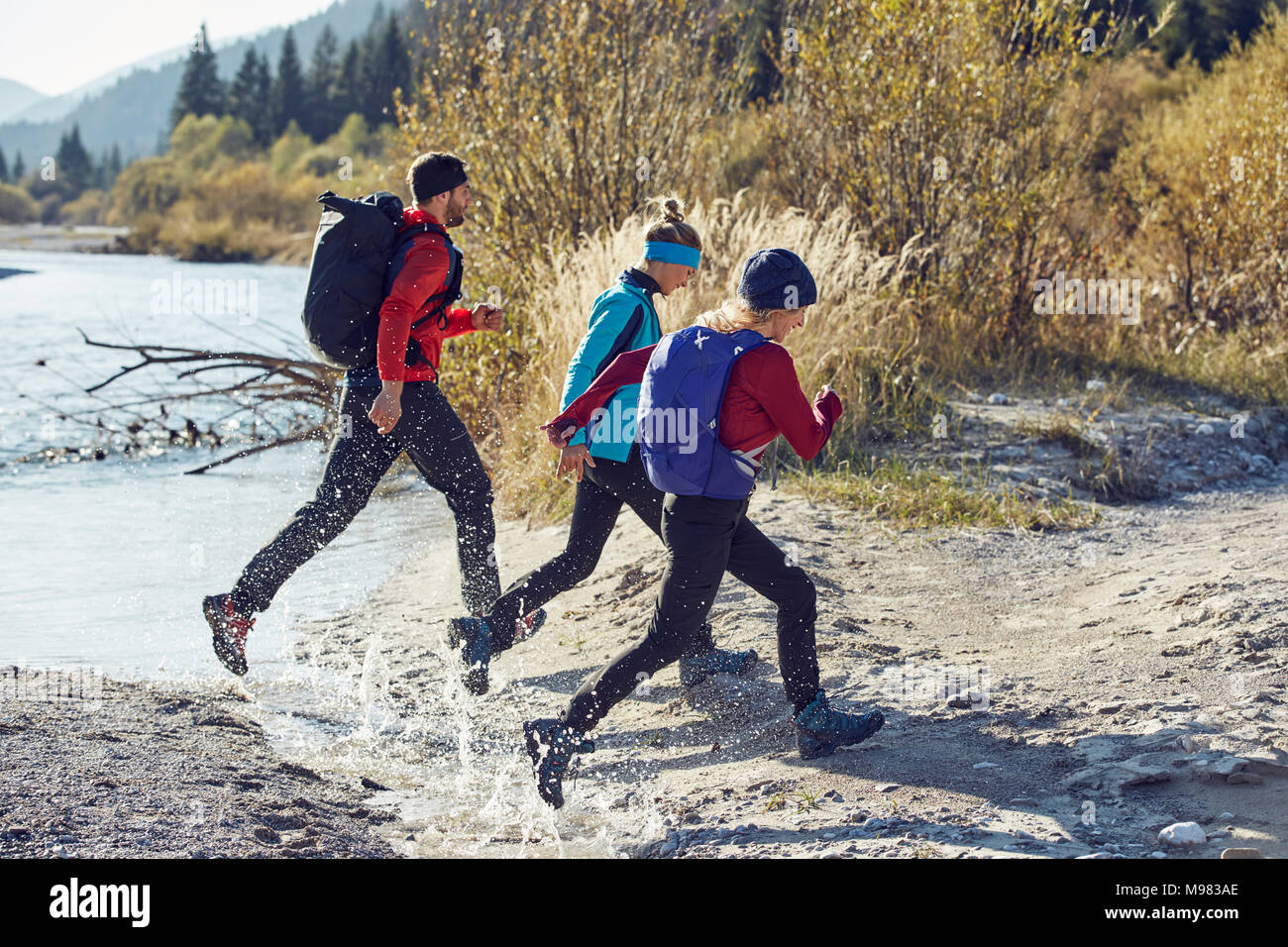 Group of friends hiking jumping over river - Stock Image