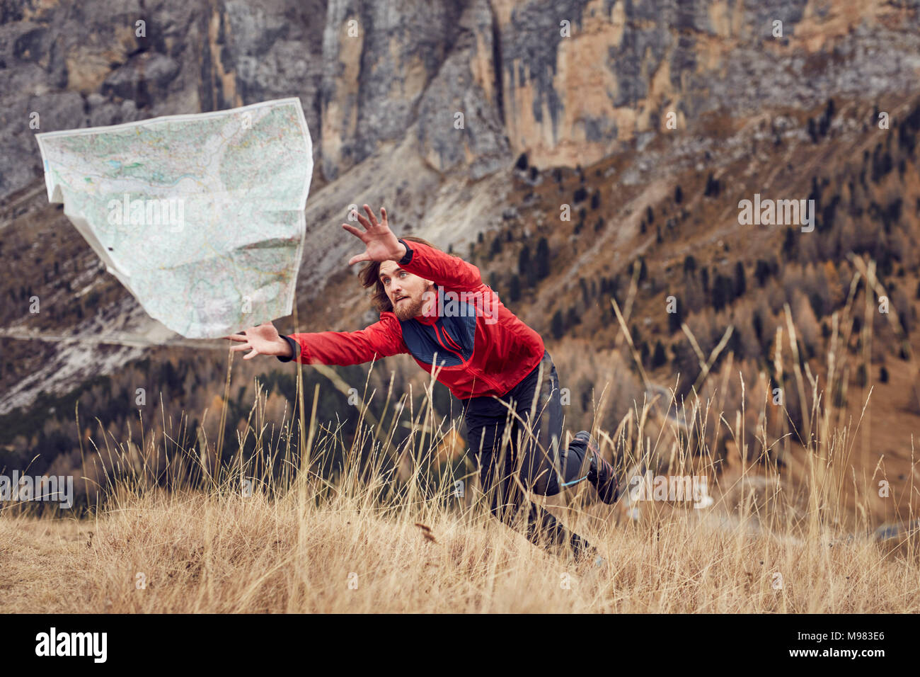 Mountain hiker chasing map flying away - Stock Image
