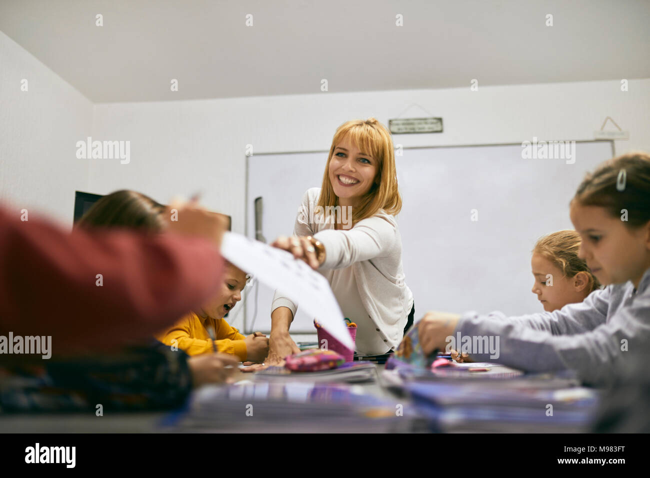 Smiling teacher handing over sheet of paper to student in class - Stock Image