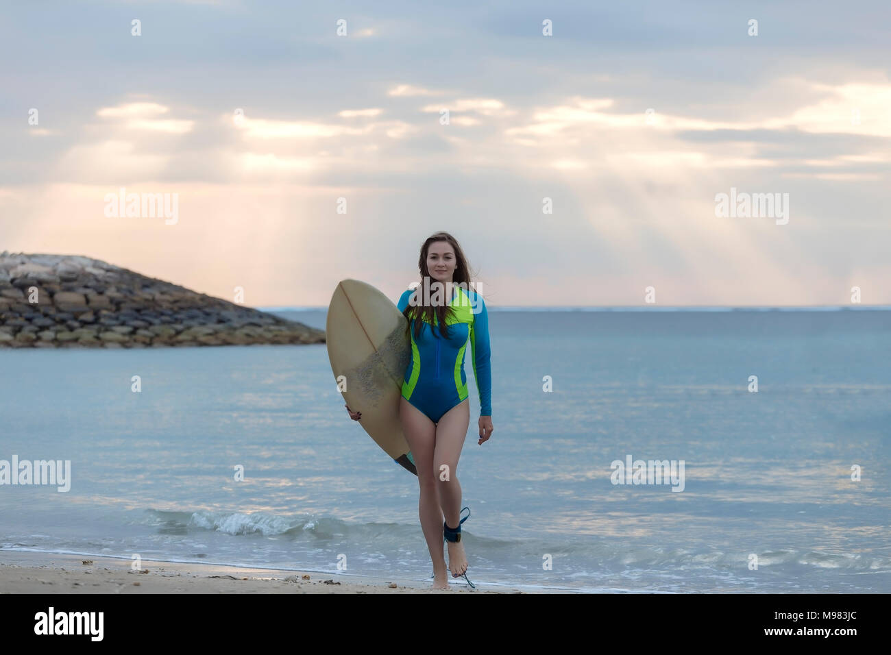 Indonesia, Bali, young woman with surf board walking at beach - Stock Image