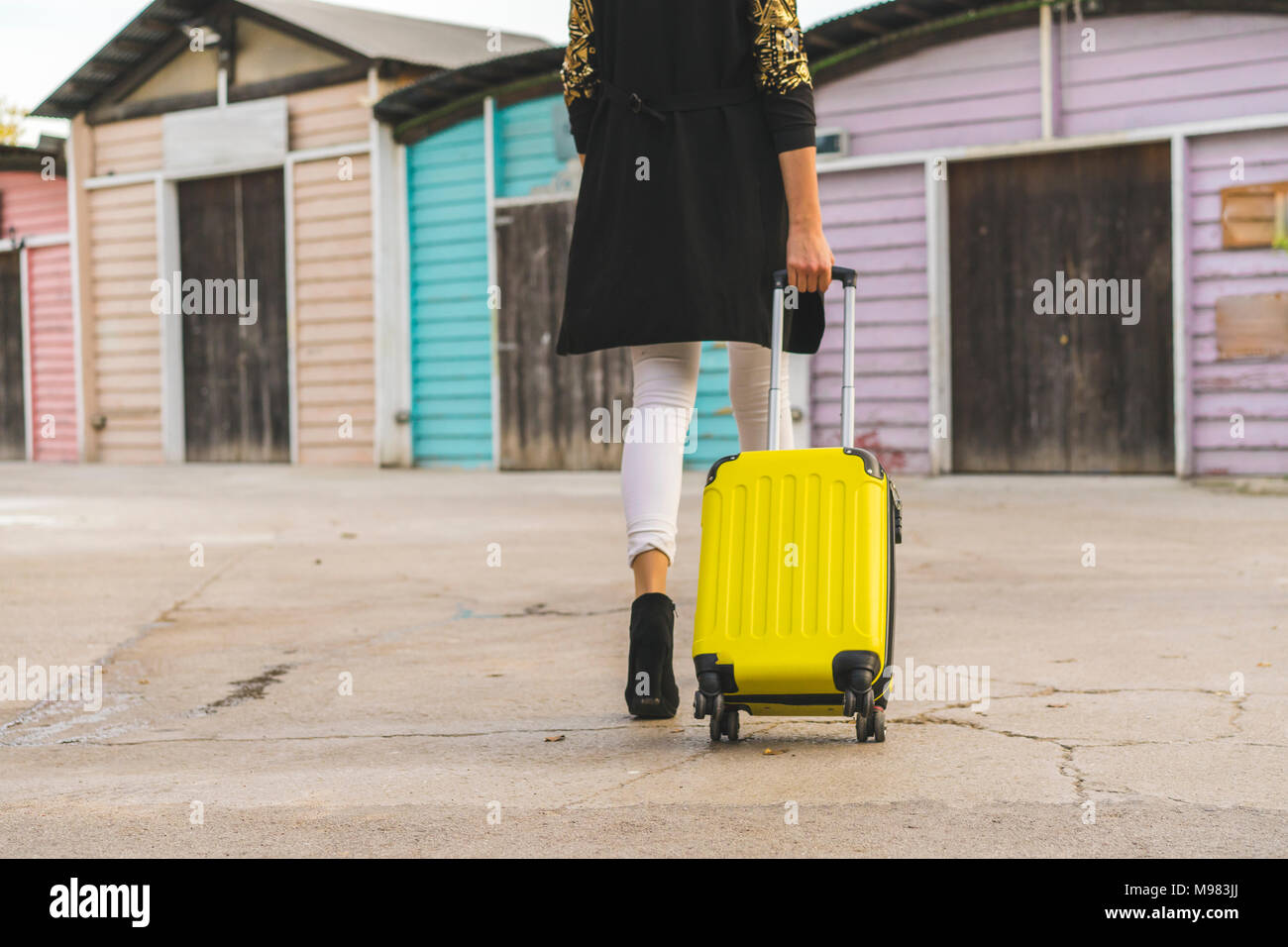 Back view of walking woman with yellow trolley bag, partial view - Stock Image