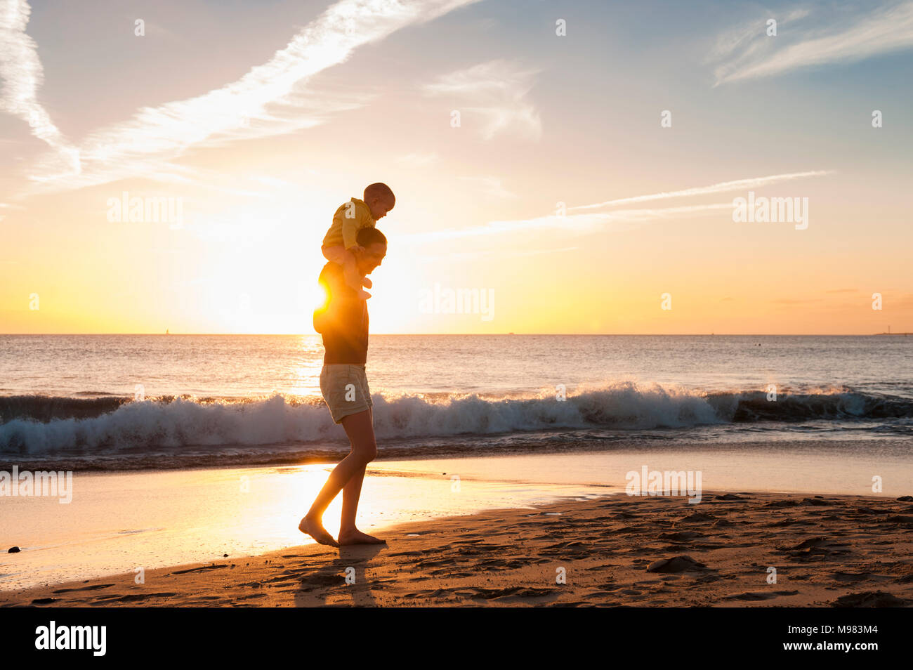 Mother walking with little daughter on the beach at sunset - Stock Image