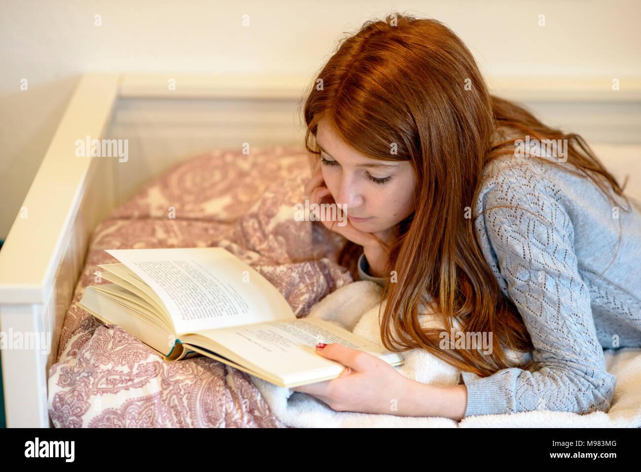Mädchen beim Lesen, liest im Bett, Bayern, Deutschlaned - Stock Image