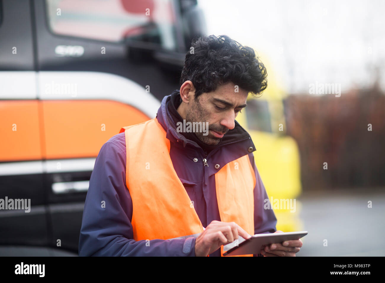 Man wearing reflective vest using tablet at trucks - Stock Image
