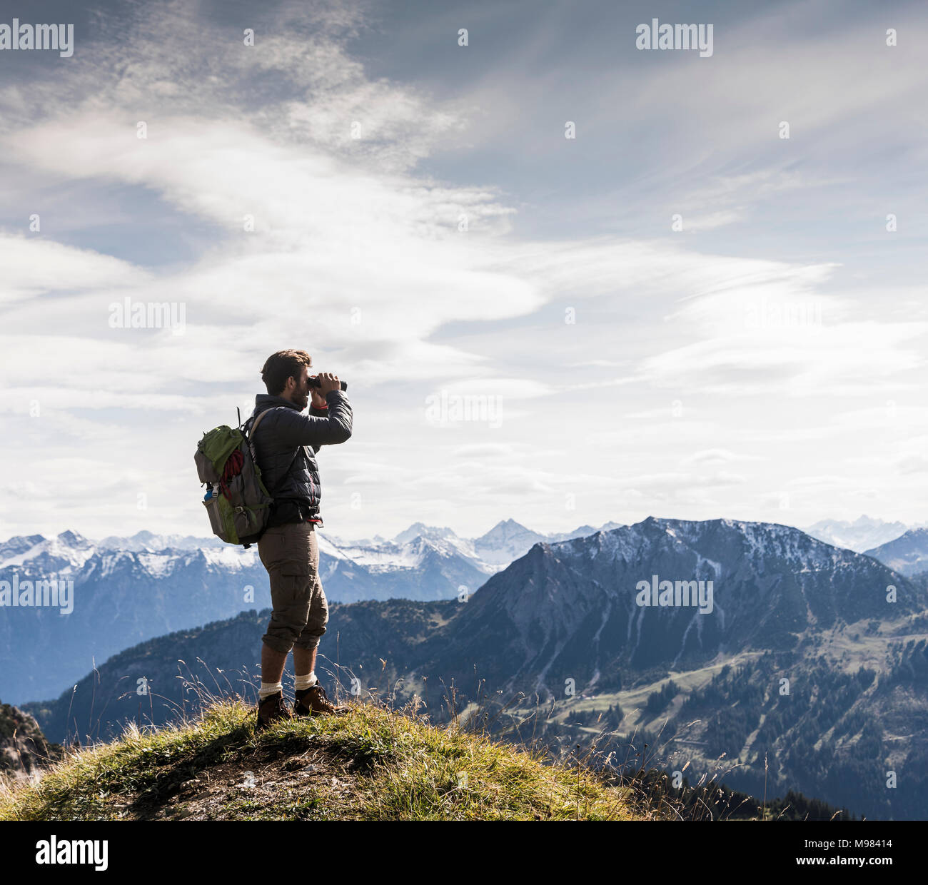 Austria, Tyrol, young man standing in mountainscape looking at view with binoculars Stock Photo