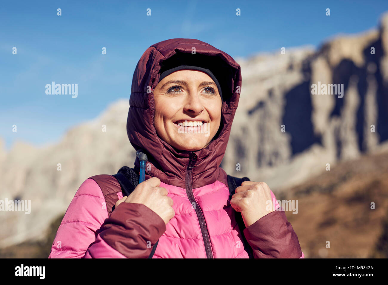 Portrait of confident young woman hiking in the mountains - Stock Image