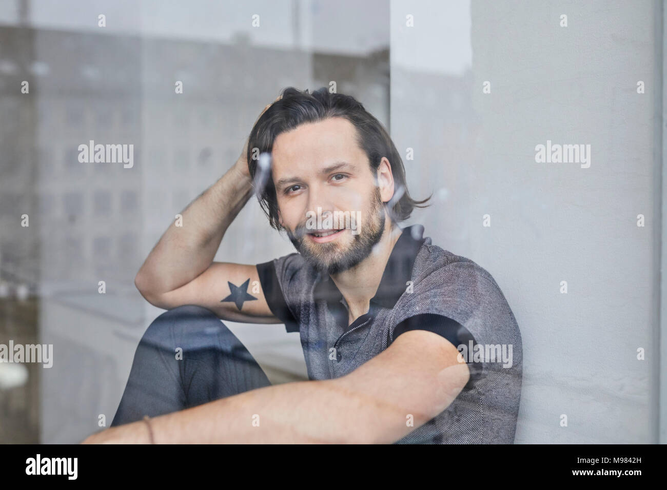 Portrait of smiling man looking out of window - Stock Image