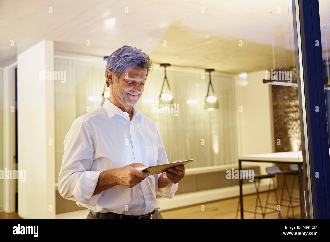 Man using tablet in modern building at night - Stock Image