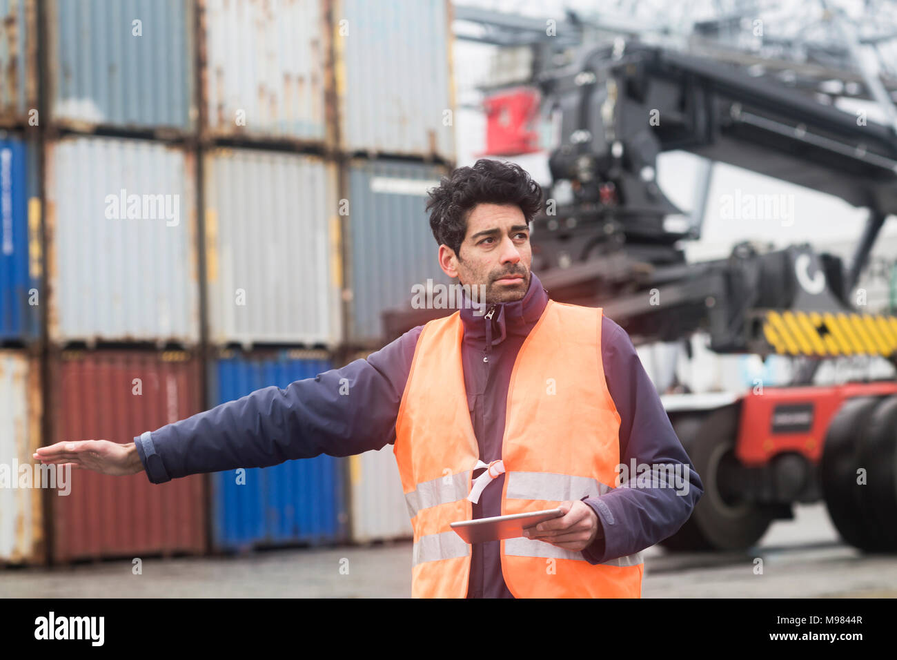 Man with tablet wearing reflective vest at container port - Stock Image